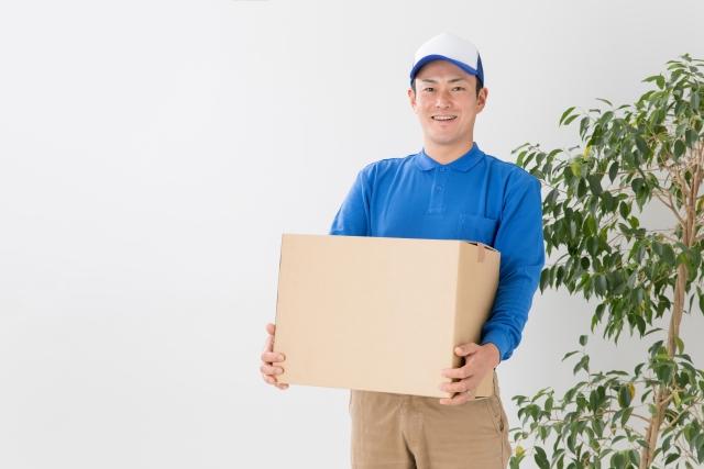 ダンボール箱を抱える男性業者