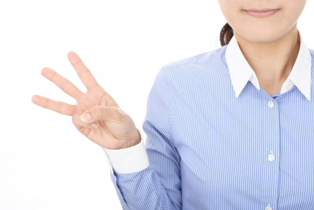 三本指をたてる女性